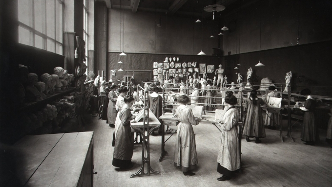 Black and white photograph of group of mainly female students with two men, working on ornamental plasterwork in an Edinburgh College of Art studio containing casts